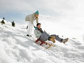 stock photo of toboggan  - Young Couple Sledding - JPG