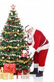 Santa Claus bringing gifts and putting under Christmas tree, isolated on white background