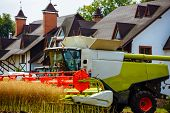 Combine Harvester In Action On The Field. Tractor And Harvester At Harvest Time. The Agricultural Se poster