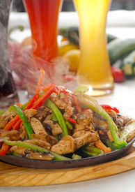 stock photo of mexican food  - original fajita sizzling smoking hot served on iron plate with selection of beer and fresh vegetables on background - JPG