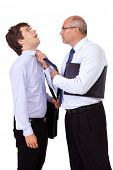 Senior angry businessman with briefcase tearing young businessman at his tie, isolated on white back