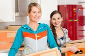 Young women - presumably friends - with moving box in her house moving in or out of a apartment, foc