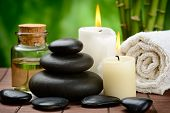 zen basalt stones and massage oil on the wooden mat