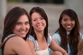 image of bff  - Three pretty teenage students smiling and sitting together - JPG