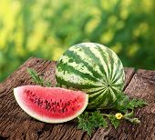 Watermelon with a slice and leaves on a wooden table. Background - blur of nature.