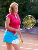 Young Woman Holding A Tennis Racket And Balls