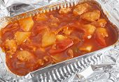 A takeaway foil bowl of Chinese sweet and sour chicken.