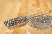 stock photo of tablespoon  - Tablespoon of chia seeds with chia seeds soaking in a glass of water  - JPG
