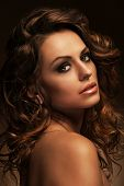 Beautiful caucasian woman with curls and evening makeup