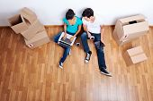 overhead view of couple sitting on floor together using computer wireless internet while moving into