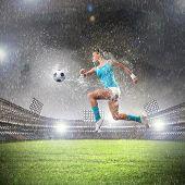 Bild der jungen Frau-Football-Spieler treffen ball