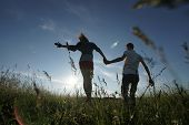 Young couple walking through green field
