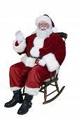 stock photo of santa-claus  - Santa sitting in rocking chair waving before his annual trip - JPG