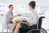 Businesswoman shaking hands with disabled colleague at desk in office