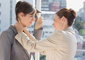 stock photo of strangled  - Businesswoman strangling another in the office - JPG