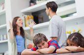 Couple arguing behind their children in the kitchen