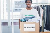 Attractive man holding a donation box full of clothes