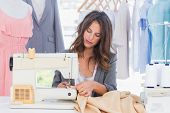 stock photo of sewing  - Fashion designer sewing with sewing machine - JPG