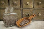 jar and scoop of chia seeds with a primitive apothecary drawer cabinet
