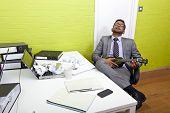 Indian businessman asleep at his desk clutching ukulele