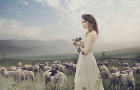picture of shepherdess  - Young pretty cheerful woman with lamb on a countryside - JPG