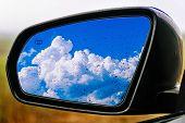 stock photo of sensory perception  - car mirror overlooking the blue cloudy sky - JPG