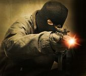 stock photo of terrorist  - masked terrorist firing a machine gun - JPG