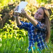 Nice teengirl in nature and taking selfie on a tablet PC