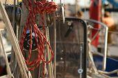 Huge bundles of rope hang alongside a wooden ship's rail