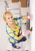 repair, renovation and home concept - smiling woman in gloves doing renovations at home