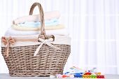 Colorful towels in basket and pins on light background