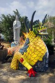 A sculpture of a dragon on the background of the statue of the goddess Guan Yin