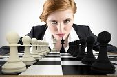 Composite image of focused businesswoman with chessboard