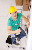 repair, building and home renovation concept - smiling man in yellow protective helmet hammering nail in wall