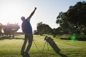 Golfer happy with his shot on a sunny day at the golf course