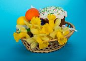 Easter cake, eggs and flowers in a basket