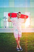 At summertime sunshine stylish hipster standing with board