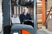 Man posing in a reach truck in a warehouse, in the background there are pallets with cardboard boxes