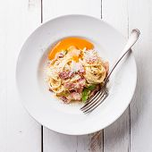 image of carbonara  - Pasta Carbonara on white plate with parmesan and yolk - JPG