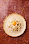 Pasta Carbonara With Parmesan And Yolk On Textured Background
