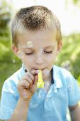 Young boy blowing bubbles outdoors