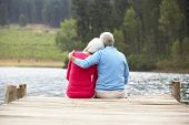 Senior couple sitting on a jetty