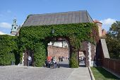 KRAKOW, POLAND - SEPTEMBER 15, 2013: Tourists under the Bernardine Gate of Wawel royal castle. Built