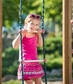 happy little girl on outdoor playground equipment
