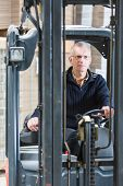Forklift driver, manning the controls and steering wheel of his forklift in a large warehouse. Just