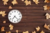 Clock And Leaves On A Brown Plank