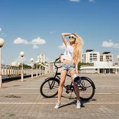 stock photo of swag  - Woman standing next to beach bicycle - JPG