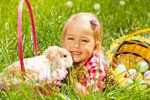 pic of cuddle  - Cute small girl cuddling rabbit in green field with basket with Eastern eggs nearby - JPG