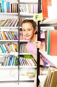 Girl looks and stands behind bookshelf in library