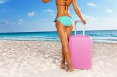 Tanned woman standing  with suitcase
